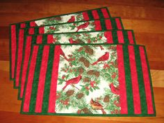 The fabric is 100% cotton (and prewashed), pretty cardinals with pinecones in the center space, each mat having a slightly different fussy-cut center placement, and the ends (or the sides) having been strip-pieced with pretty Moda Marbles green and red fabrics. The backing fabric is a pretty holly-on-black and certainly making these mats reversible. 100% poly fusible fleece batting. These mats are channel-quilted with coordinating thread and a machine decorative wavy stitch. The traditional…