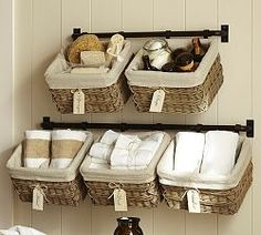 Pottery Barn.  What a great idea to hang baskets from a metal rod.  Great for kitchen, laundry room, bath.  Can think of lots of things to put in them at a fingertip reach.