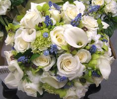 Green miniature Hydrangeas & Orchids, Ivory Ruffled Roses, Calla Lilies, Freesia, Muscari and Blue Paves