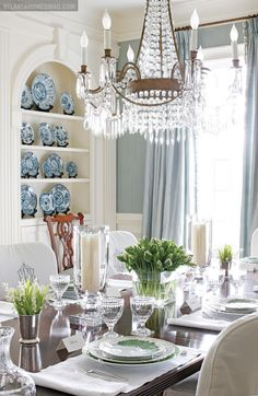 """The stylish table setting in the dining room features glass hurricanes and crystal stemware by William Yeoward. """"Greenleaf"""" china by Anna Weatherly, one of the many patterns Elsey has collected over the years, is set upon custom linens, their monograms matching those of each slipcover. A display niche featuring Chinese porcelain plates from Jane Marsden Antiques is further evidence of Elsey's passion for delicate tableware.   Atlantahomesmag.com"""