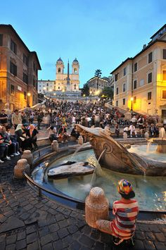 In the evening at the Bernini fountain on the Piazza de Spagna and the Spanish steps, Rome, Italy