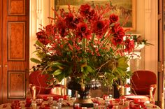 Goodwood House Front Hall - urn filled with red amaryllis and berries with winter foliages.  Flowers by Matthew Spriggs