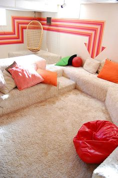 I love this...conversation pit, shag carpeting, orange pillows and beanbags, hanging chair.. the Arrow on the wall... can you get much better???