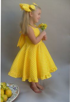 A beautiful dress made with yellow and white polka dot fabric. The sleeveless shoulder straps ties at the back with a big bow. This dress