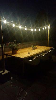 Terras met romantische verlichting en zelfgemaakte tafel van eiken houten balken en steigerbuizen