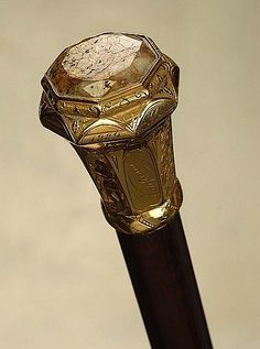 """A very important California gold quartz presentation cane with engraved scenes. The large solid gold knob handle is 2 1/4"""" high and 1 3/4"""" at its widest. Inlaid on the top is a 1 1/8"""" polished and faceted gold quartz stone with lots of polished gold flecks in the matrix.  1860 presentation is inscribed on the side panels: """"S. C. Fogus to A. C. Wilgus / California."""" (Shelton C. Fogus was one of the original pioneers who crossed the Plains by covered wagon and arrived in California in 1849."""