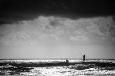 Jetty Fisherman Under A Galveston Storm http://mabrycampbell.com #image #photo #galveston #texas #MabryCampbell #fisherman #storm #coastline #morning #gulfofmeico #water #silhouette #morning #dark #blackandwhite #moody