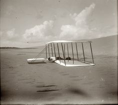 1901. Kitty Hawk, North Carolina. Wilbur Wright and glider just after landing. 4x5 dry-plate glass negative attributed to Orville Wright. The fogging of the negative at the bottom of the frame, combined with the skid marks in the sand from an earlier landing, create the illusion that the glider is still flying.