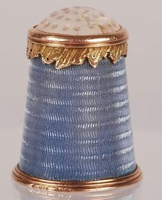 Pale blue guilloché enamel over rose gold thimble with wavy band of fine yellow gold filigree, set with white stone top. Michael Perchin, Fabergé, St. Petersburg, c. 1890. John Atzbach Antiques, Redmond, WA. $22,500.