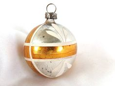 This vintage Christmas ornament is a small, round silver ball with a white framed gold cross around it.