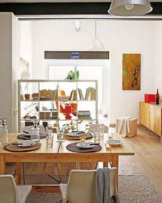 Эта квартира оригинально спроектирована и наполнена индивидуальностью. Высокие потолки, беревянные балки, трубы и большое количество цвета – всё это способствует неповторной атмосфере. Благодаря правильному, экономному распределению места, каждый угол в этой маленькой квартире максимально полезно использован. Всё внимание сфокусировано на якро-оранжевом кресле и стуле – очень удобном уголке для чтения около окна.
