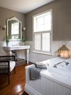 Traditional Master Bathroom Putty-hued paint stands out against crisp white panelling.A cushioned wicker chair is a cosy addition to this master bathroom. The warm wood floor, ornate mirror and lantern candle holder gr Bad Inspiration, Bathroom Inspiration, Home Design, Design Ideas, Interior Design, Beadboard Wainscoting, White Beadboard, Bathroom Beadboard, Modern Farmhouse Bathroom