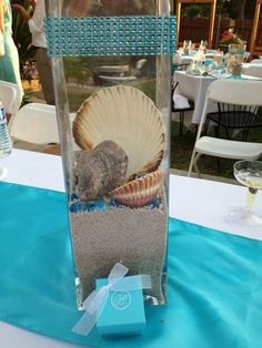 Like the idea of a different centerpieces for each table.  Love this but it needs flowers. Beach theme wedding-different centerpiece per table!
