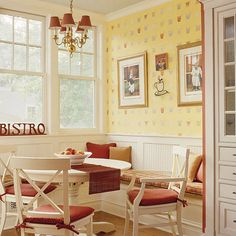 Sunny Breakfast Nook  An inviting breakfast nook with lots of windows protrudes from the back of the house, capturing plenty of light. The space is wrapped in wainscoting, lending it a cozy, cottage feel. The archway cabinets hold party supplies for entertaining.