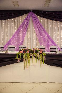 Fehér és lila háttérdekoráció az esküvői főasztal mögé. Dupla masni színben harmonizáló főasztaldísz egészíti ki.