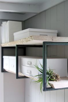 office shelving made of three square steel frames that were acid washed and fitted with unfinished ash slabs.