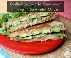 Un sándwich de aguacate a la plancha con tomate fresco y rúcula y rica, mayo sriracha picante.  El almuerzo se sirve, todos ustedes.