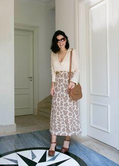 Look da Alice Ferraz com saia midi e camisa de manga comprida branca. Acessórios em marrom