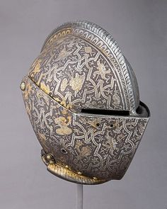 Milanese closed helm for combat (c. with a whole lot of intricate, acid etched, designs of weapons, instruments and mythological symbols.