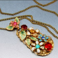 Gorgeous 1920s Czech Art Deco gold gilt enamel rhinestone jeweled necklace. The pendant features an gold gilt filigree drop with three dimensional enamel flowers having amethyst purple, ruby red, golden amber and sapphire blue rhinestones. Each flower is totally different with the pendant suspended from a pink enamel flower bale having green enamel leaves. A brass twisted wire chain with screw barrel completes the piece.