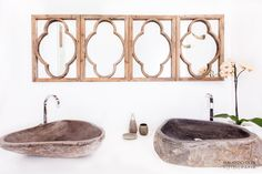 Vintage mirrors,combined with natural stone basins and cow horns as towel hooks (visible in the mirror reflection)