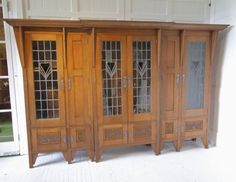 Glasgow School large rare 3 section display bookcase Oak with leaded glass panel doors Central coloured heart shaped glass and lower carved panel doors Distinctive Morris metalwork Designed by Talwin Morris Featured in The Studio Magazine 1908