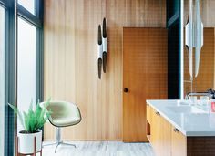 A chair, upholstered in Checker by Alexander Girard for Maharam, adorns the master bathroom of this Portland residence.    This originally appeared in Midcentury Renovation in Portland Capitalizes on Nature with Seven Doors to the Outside.