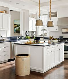 Designer Kevin Scanlon crafted the pendant lamps in this South Carolina kitchen out of crab baskets, rope, and burlap. Bright idea: When it comes to handsome trash cans, nothing tops an antique butter churn.   - CountryLiving.com