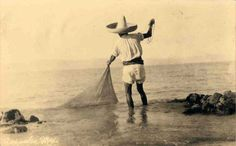 man fishing with a cast net on the rocks at Acapulco Mexico. The fishermen of this region still fish in this manner todayl