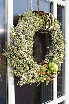 Der Kranz aus weißen Erica gracilis wurde mit Filzbändern, farbigem Aludraht, Hortensien, Ziergurken, Laub und einer Artischocke verziert.