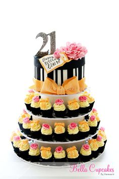 The classy black and white vintage hat box (this time with varied-width stripes) decorated for a girl's 21st birthday with glittery numbers and a subtle complementary pink and peachy-yellow color scheme cupcake tower.