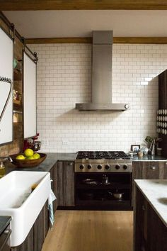 Sliding doors conceal shelving, vintage farm sink, wall of subways - Ellen & Greg's Renovated Loft Kitchen Kitchen Tour | The Kitchn