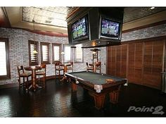 1445 W Grande Cir #7, Washington, UT   Home for sale: $8,495,000    Channeling the atmosphere of a classic sports bar, this man cave has tall bar tables and chairs, a pool table, dark hardwood floors, and — in a nod to the massive scoreboards found in many sports arenas — there is a drop-down bank of four TVs mounted from the ceiling, which offers a 360-degree view of the game