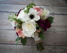 This rustic wedding bouquet is arranged with blush and ivory garden roses, anemones and peonies, with pops of blush peonies and plum ranunculus, accented with greenery and astilbe. This wedding bouque