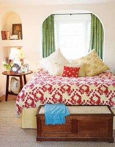Kathryn Ireland's Bold and Bright Ojai Home.  In the master bedroom, it's pattern on pattern: The bedspread is Ireland's Ikat red fabric and the pillows are a mixture of her fabrics. The curtains are her Floral Jacquard Killip. Blue cashmere throw from J. Roaman. The lampshade is made from a Robert Kime fabric, 12 Colors. Carpet is wall-to-wall wool sisal.