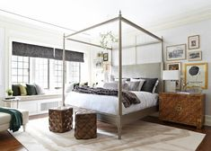 Stunning bedroom features gray molding trimmed walls lined with an eclectic gallery wall which frames a gray canopy bed laden with white and gray bedding and a gray faux fur throw alongside a burl wood chest of drawers topped with a modern block table lamp.