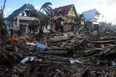 People walk among debris and destroyed houses in Palo, eastern island of Leyte on November 10, 2013, three days after devastating Super Typhoon Haiyan hit the area on November 8. The death toll from a super typhoon that decimated entire towns in the Philippines could soar well over 10,000, authorities warned on November 10, making it the country's worst recorded natural disaster.