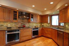 Omega inset cabinets in a cerused pecan finish. Fusion quartzite countertops. Multi-colored slate backsplash