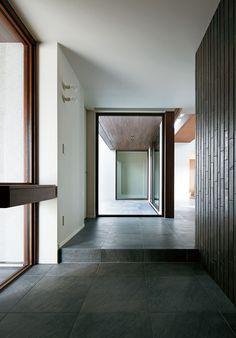 石調タイルの床が土間から続く玄関。右手が階段ホール。戸外のテラス越しに向こうの廊下へと視線が抜ける。