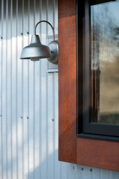 i love the warm wood/dark window with the corrugated siding