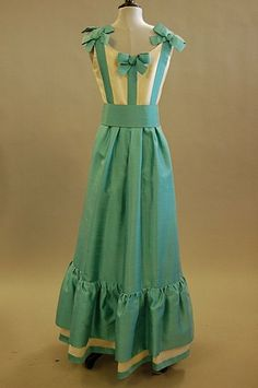 A Jean Patou Paris turquoise and ivory slubbed silk dress, late 1960s, labelled and numbered 86453, the bodice trimmed with bows to front and back and shoulders, deep flounced hem, broad belt. Back