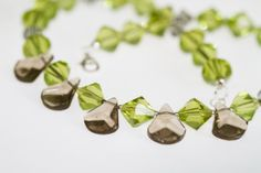 Closeup jewelry photography of a necklace made with translucent green and tan jewels.