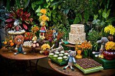 Para reforçar o tema do aniversário, uma floresta de crochê, a mesa do bolo foi montada na frente de um paredão repleto de plantas. Feito por Bruna Gauss (www.facebook.com/pages/Bruna-Gauss-Arte-em-Açúcar), o bolo era um pão-de-ló com recheio de doce de leite, abacaxi e coco. A cobertura era de marshmallow com coco queimado