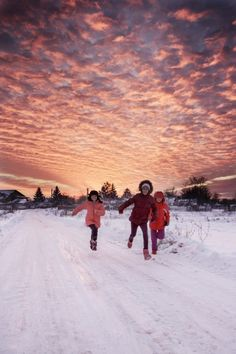 Winter sunset with children running in the snow