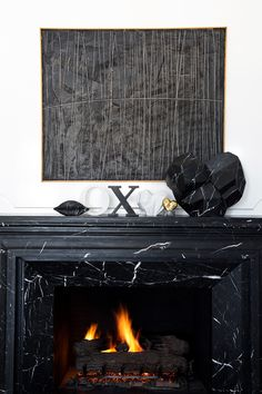 A bold, dark black fireplace definitely makes a statement. The abstract wall art & mantel pieces perfectly complement this dashing, somewhat masculine, fireplace design. House Styles, Marble Fireplaces, Fireplace Design, Home And Living, Living Room With Fireplace, White Living, Black Fireplace, Home Decor, Kelly Wearstler