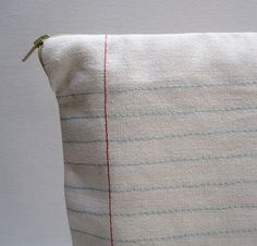 Sew blue and red lines to make fabric look like lined paper.
