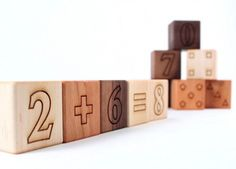 """For your littlest tot, use these natural, organically finished and sustainably sourced number blocks to introduce number concepts. The 12 piece set includes 10 number blocks (for numbers 0-9), one """"equals"""" block, one 4-sided block with each side devoted to addition, subtraction, multiplication, and division, and a cotton bag to keep everything together."""