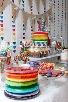 rainbow birthday party  notice the cake in the back?  I like the idea of being able to see the rainbow layers on the outside not just the inside this is such a great idea.