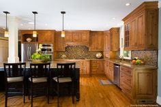 Plenty of seating at the island makes it easy to cook and entertain.  The mantle style hood provides additional storage and creates visual interest along a long run of cabinetry.  (Photo by Gregg Willett Photography)
