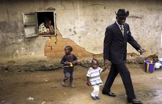 Willy Covari, one of the most admired sapeurs of the Bacongo neighborhood, walks with his two children in his plot.